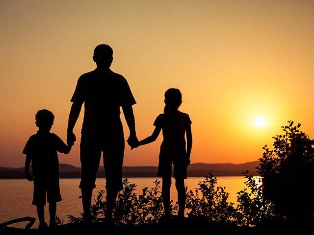 father and children at sunset