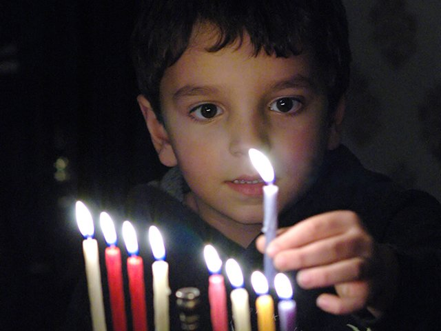 child lighting menorah