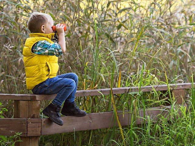 Child with binoculars at sleep away camp